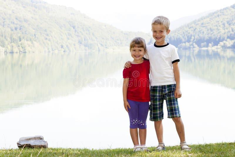 Niño pequeño feliz y hermano y hermana sonrientes de la muchacha que colocan a HU foto de archivo
