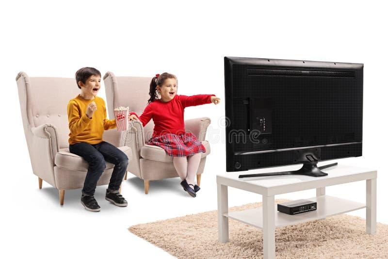 Niño pequeño feliz y muchacha que se sientan en una butaca que ve la TV y que come las palomitas fotos de archivo libres de regalías