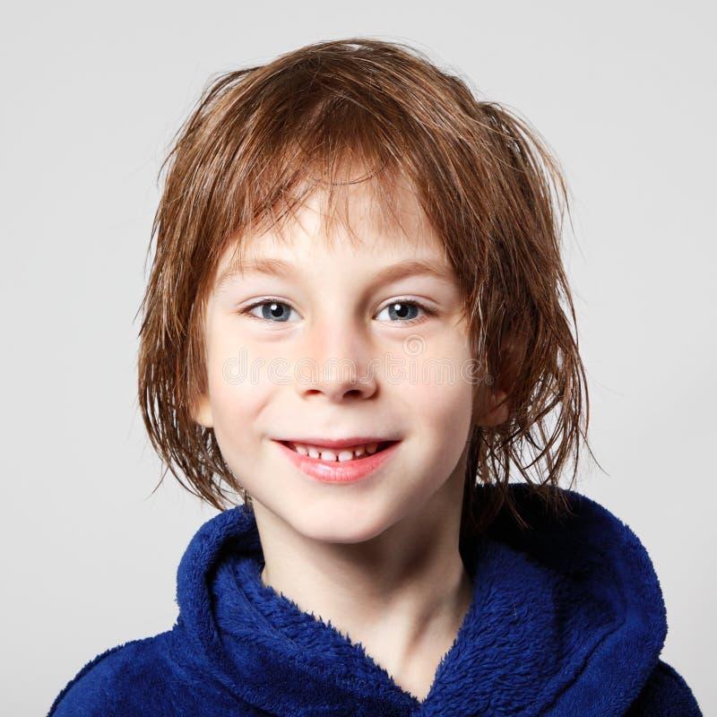 Niño pequeño hermoso después de ducha en albornoz azul con el pelo mojado foto de archivo libre de regalías