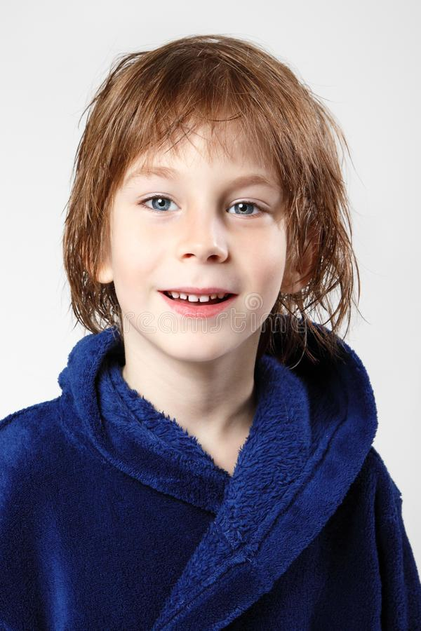 Niño pequeño hermoso después de ducha en albornoz azul con el pelo mojado imagenes de archivo