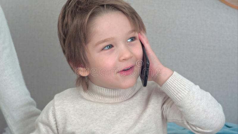 Niño pequeño hermoso que habla en el teléfono imagen de archivo libre de regalías
