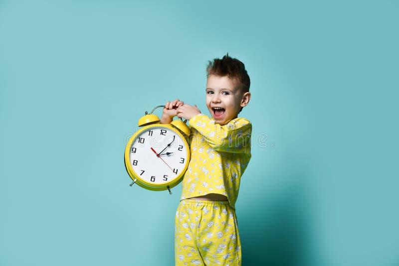 Niño pequeño lindo con el despertador, aislado en azul Niño divertido que señala en el despertador en la mañana imagen de archivo