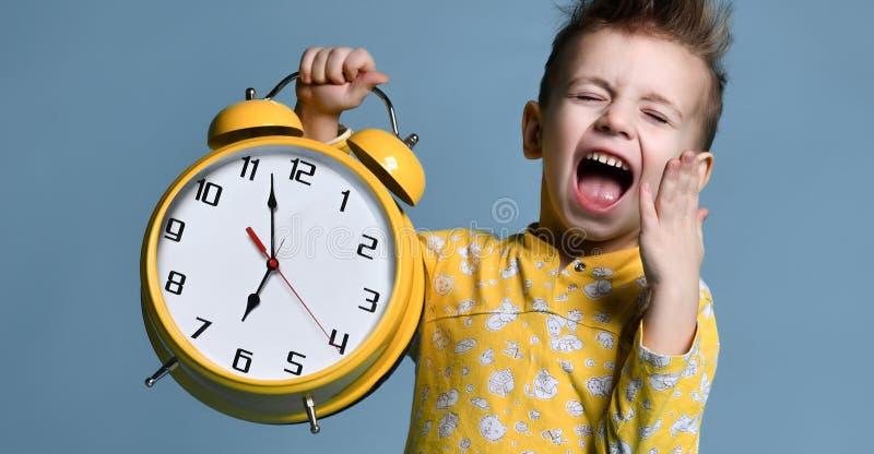 Niño pequeño lindo con el despertador, aislado en azul Niño divertido que señala en el despertador a las 7 en la mañana imagen de archivo