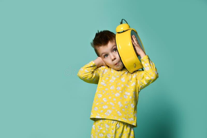 Niño pequeño lindo con el despertador, en azul Niño divertido que señala en el despertador en la mañana fotos de archivo