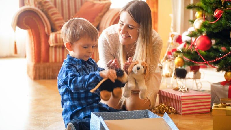 Niño pequeño lindo con el júbilo de la madre de los regalos y de los presentes de la Navidad de Papá Noel foto de archivo
