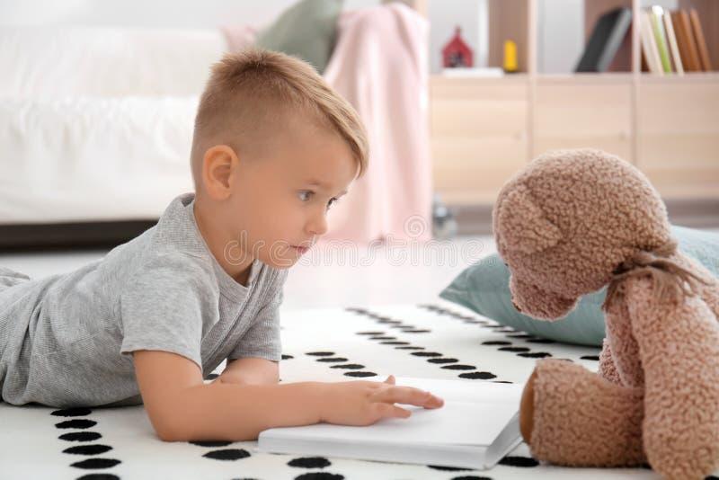Niño pequeño lindo con el libro de lectura del oso de peluche en piso en casa fotografía de archivo libre de regalías