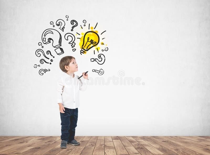 Niño pequeño lindo con el marcador, signos de interrogación, idea fotografía de archivo libre de regalías