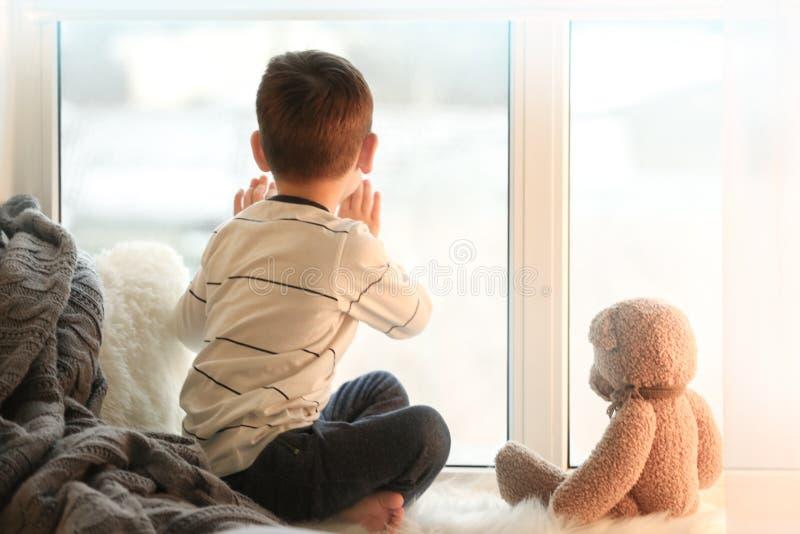 Niño pequeño lindo con el oso de peluche que se sienta en travesaño de la ventana imagenes de archivo