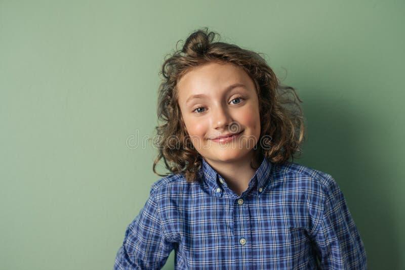 Niño pequeño lindo con el pelo rizado largo que sonríe con confianza foto de archivo