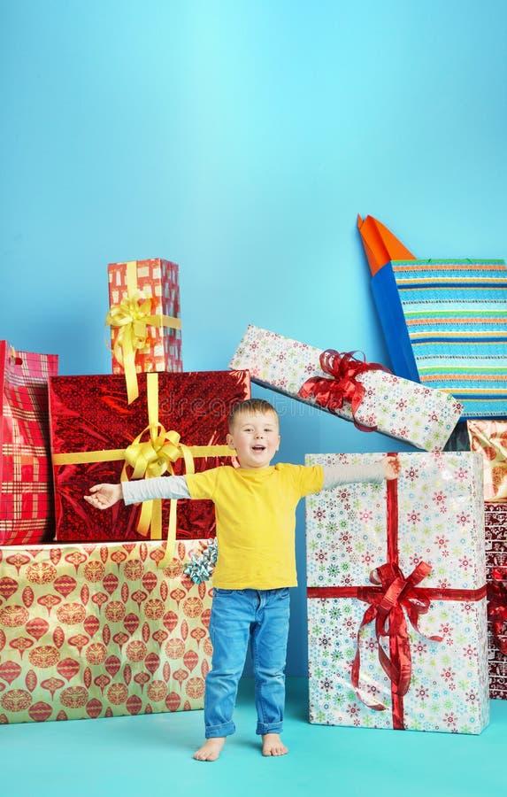 Niño pequeño lindo con el un montón de regalos fotos de archivo