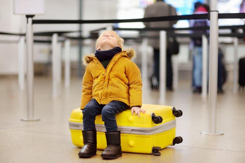Niño pequeño lindo con la maleta amarilla grande en el aeropuerto internacional antes del vuelo fotografía de archivo