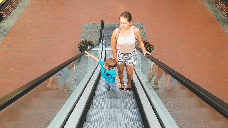 Niño pequeño lindo con la situación joven de la madre en la escalera móvil en el centro comercial foto de archivo