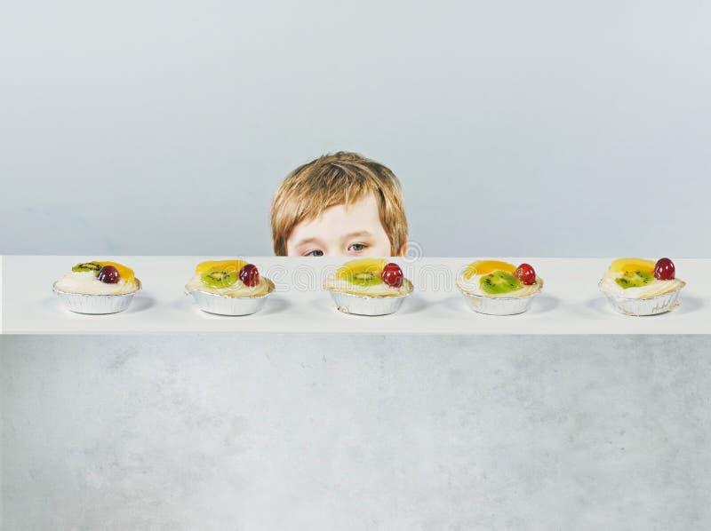 Niño pequeño lindo con la torta deliciosa foto de archivo
