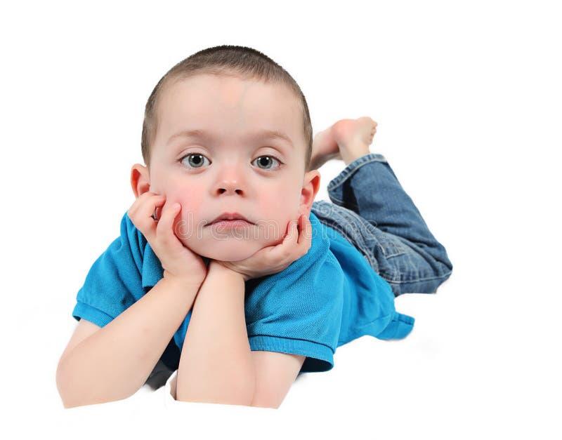 Niño pequeño lindo con las manos bajo la barbilla imagen de archivo