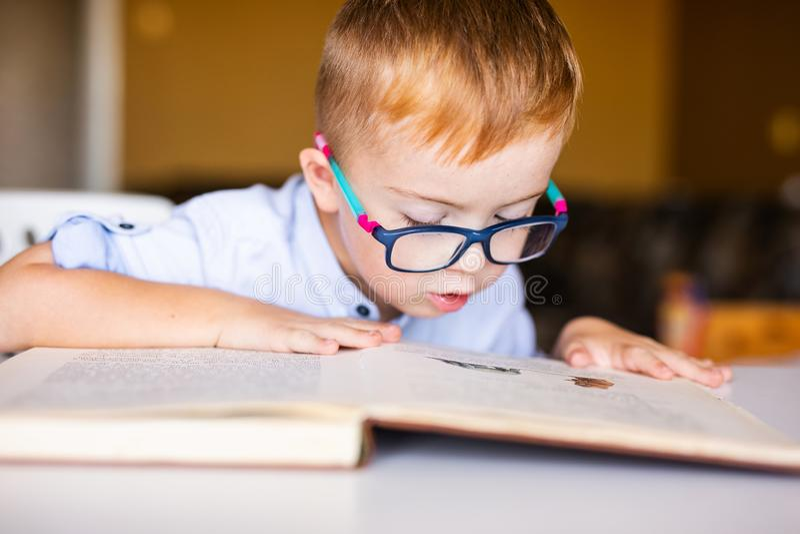Niño pequeño lindo con Síndrome de Down con los vidrios grandes que lee el libro intesting imagen de archivo libre de regalías