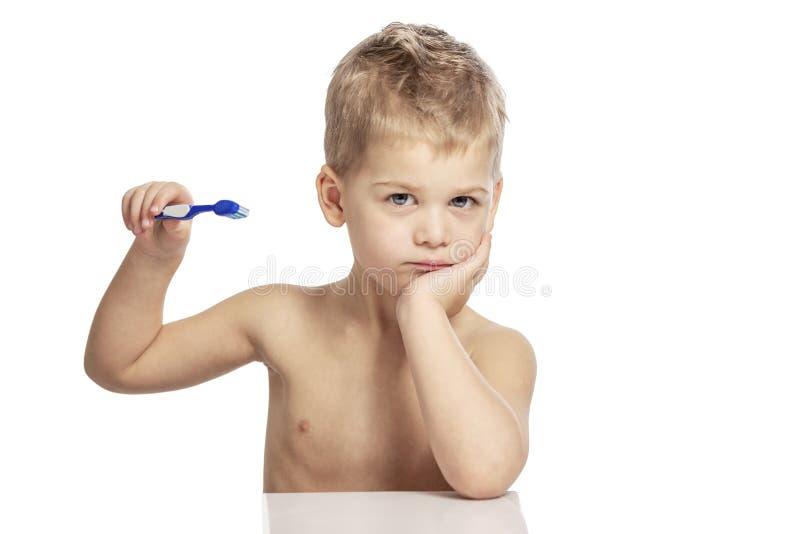 Ni?o peque?o lindo con un cepillo de dientes en sus manos Primer Aislado en un fondo blanco fotografía de archivo