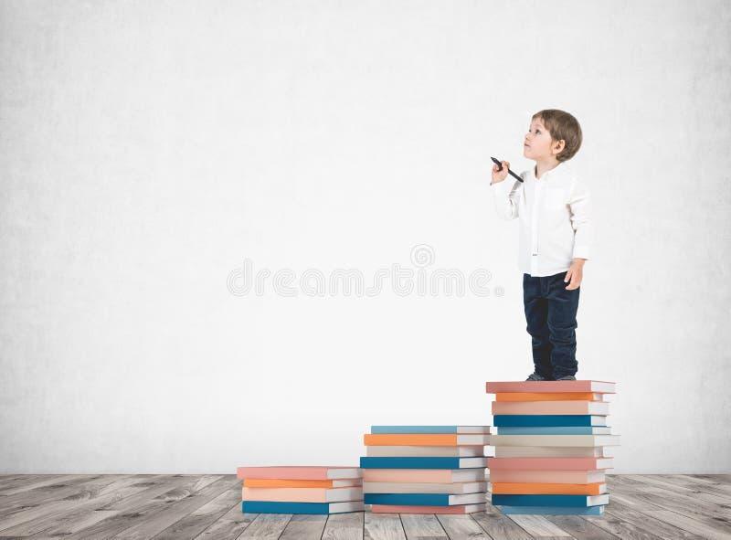 Niño pequeño lindo con un marcador en pila de los libros foto de archivo