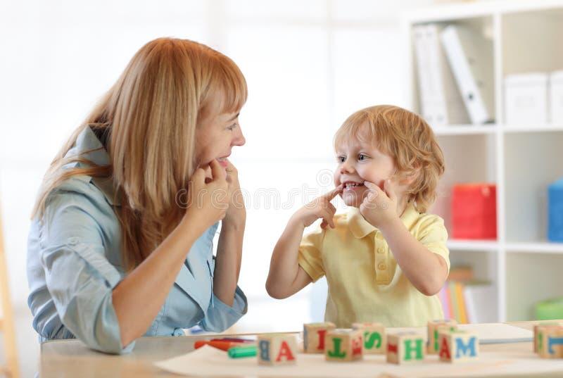 Niño pequeño lindo del niño en la oficina del terapeuta de discurso imagenes de archivo