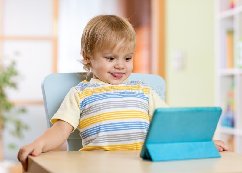 Niño pequeño lindo del niño con PC de la tableta imagenes de archivo