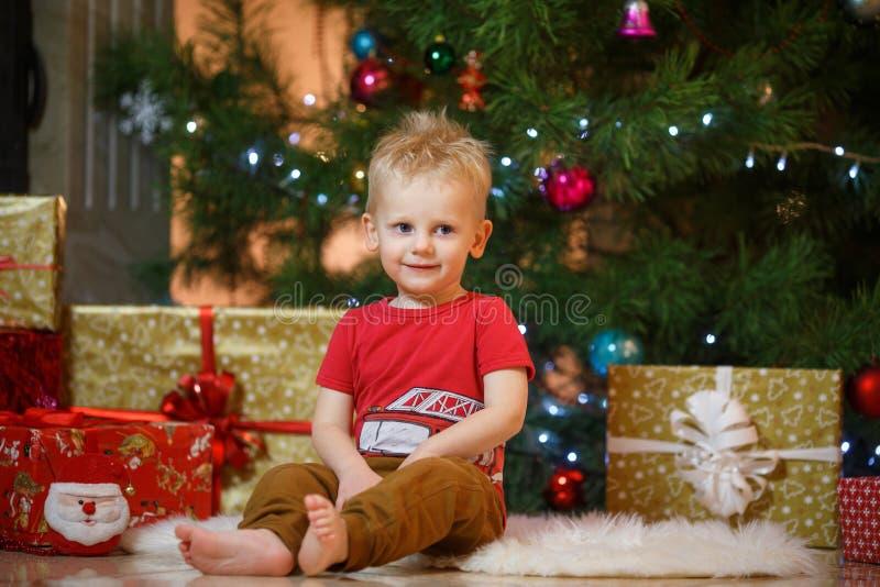 Niño pequeño lindo del pelo rubio cerca de la chimenea y de los regalos debajo del árbol de navidad imágenes de archivo libres de regalías