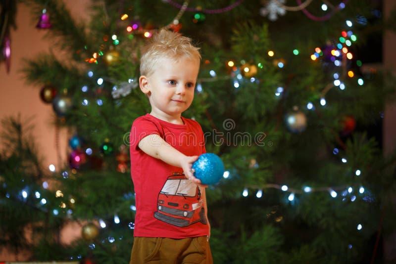 Niño pequeño lindo del pelo rubio cerca de la chimenea y de los regalos debajo del árbol de navidad foto de archivo libre de regalías