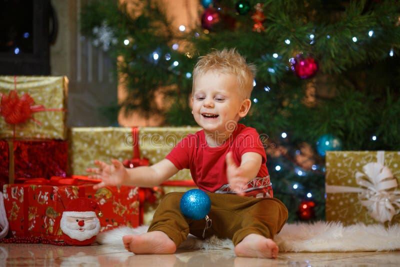 Niño pequeño lindo del pelo rubio cerca de la chimenea y de los regalos debajo del árbol de navidad fotografía de archivo