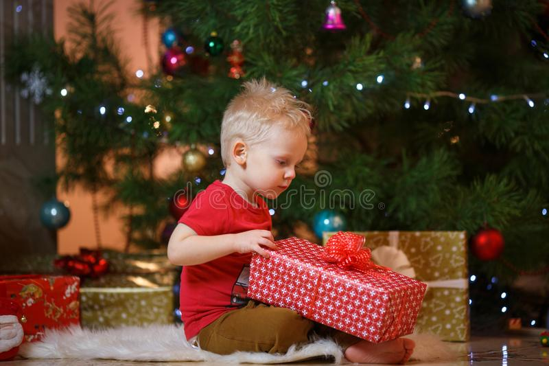 Niño pequeño lindo del pelo rubio cerca de la chimenea y de los regalos debajo del árbol de navidad imagen de archivo