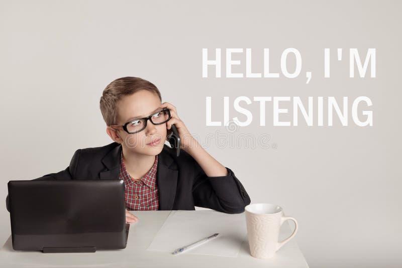 Niño pequeño lindo en un traje que habla en el teléfono foto de archivo