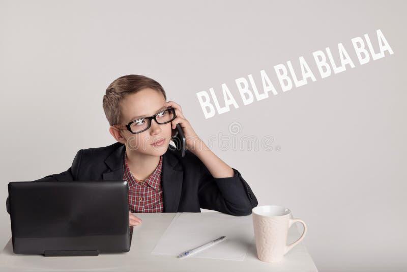 Niño pequeño lindo en un traje que habla en el teléfono fotografía de archivo