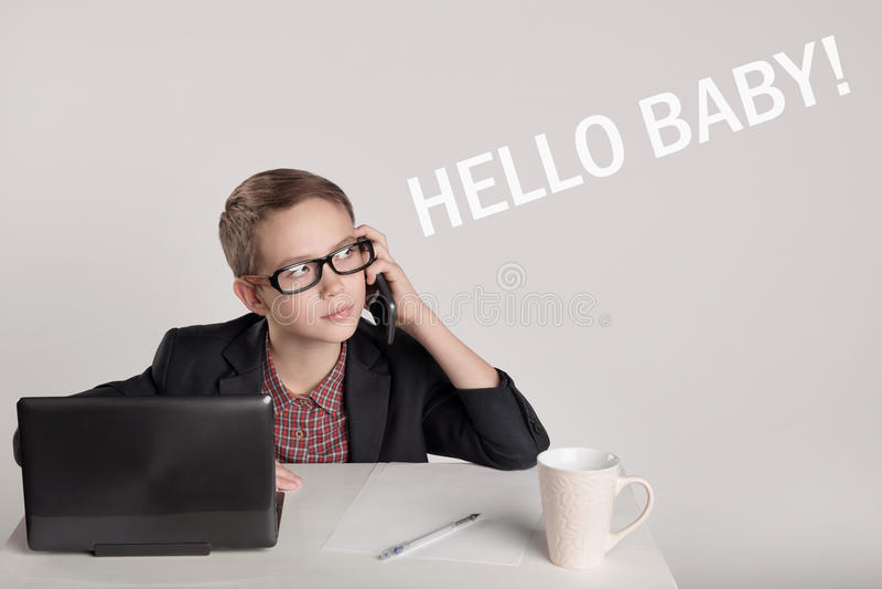 Niño pequeño lindo en un traje que habla en el teléfono fotografía de archivo libre de regalías