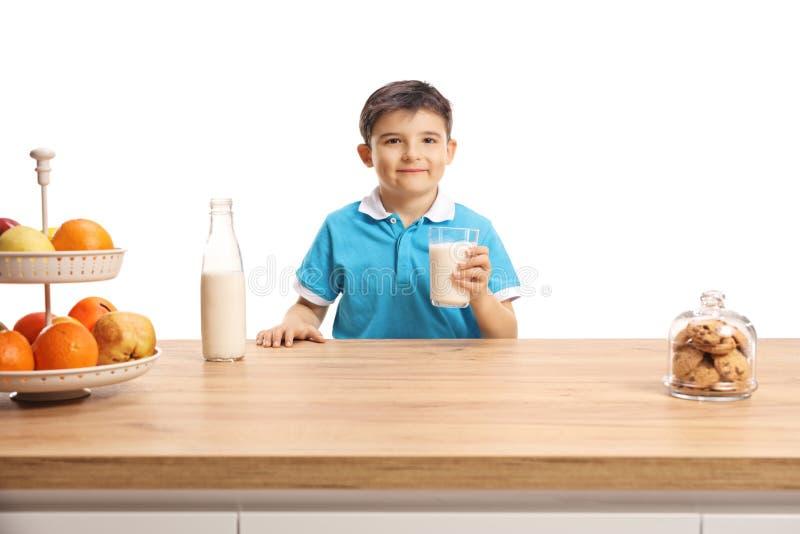 Niño pequeño lindo en una camiseta azul que sostiene un vidrio de leche detrás de un contador de madera foto de archivo