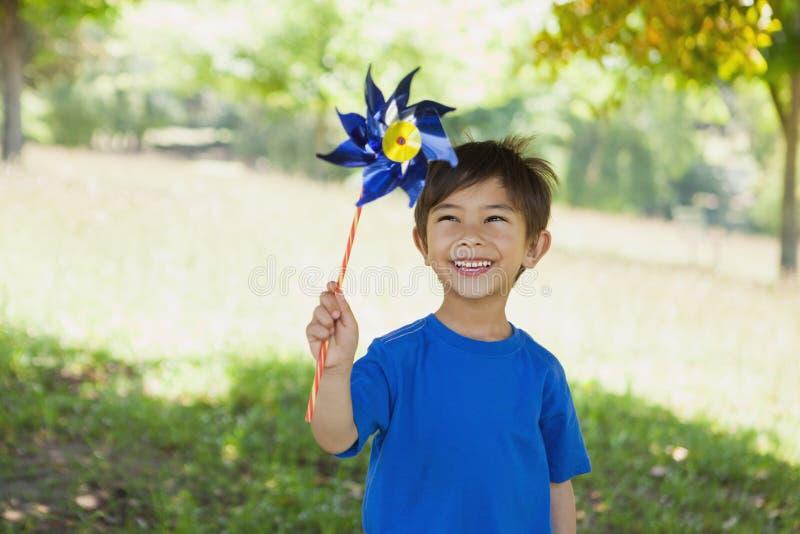 Niño pequeño lindo feliz que celebra el molinillo de viento en el parque fotografía de archivo