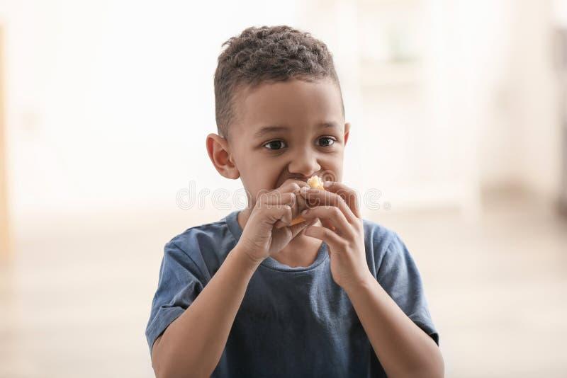 Niño pequeño lindo que come el pedazo de pan en fondo borroso imagenes de archivo