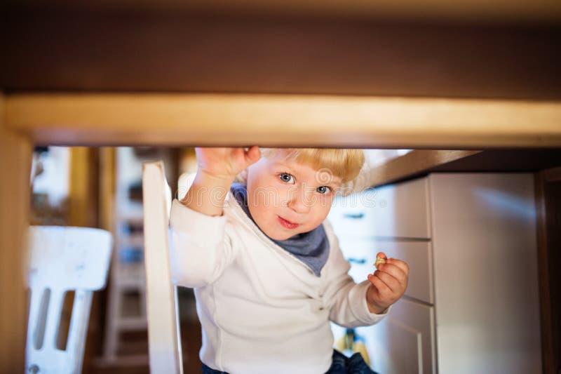 Niño pequeño lindo que come los dulces debajo de la tabla imágenes de archivo libres de regalías