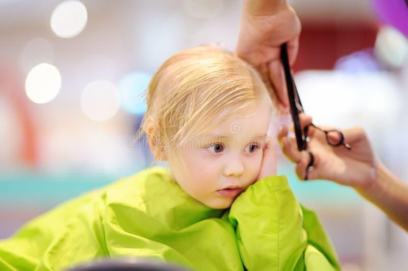 Niño pequeño lindo que consigue su primer corte de pelo imagen de archivo