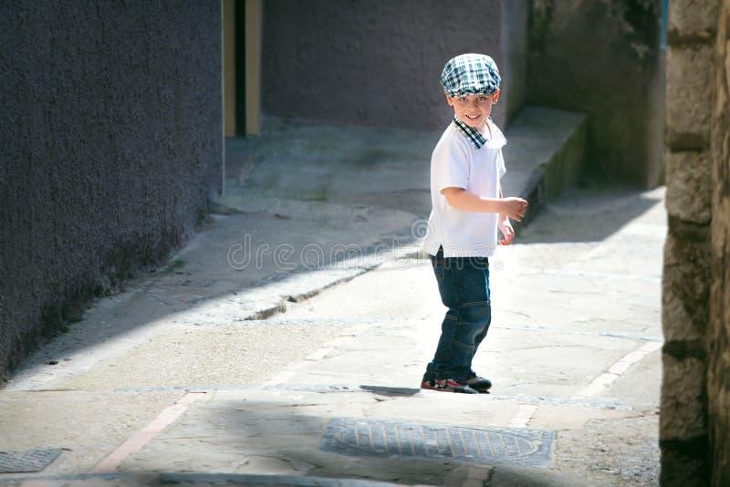 Niño pequeño lindo que cruza la calle estrecha imagen de archivo libre de regalías