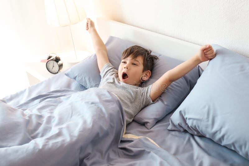 Niño pequeño lindo que estira en cama fotografía de archivo libre de regalías