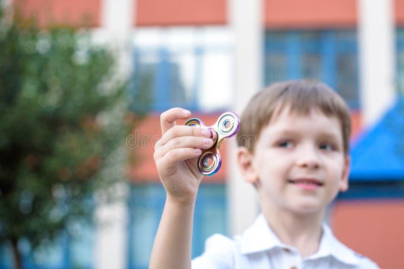Niño pequeño lindo que juega con el hilandero de la mano de la persona agitada en día de verano Juguete popular y de moda para lo imágenes de archivo libres de regalías