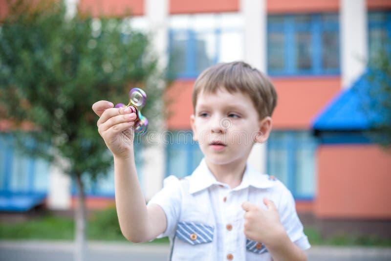 Niño pequeño lindo que juega con el hilandero de la mano de la persona agitada en día de verano Juguete popular y de moda para lo imagen de archivo libre de regalías