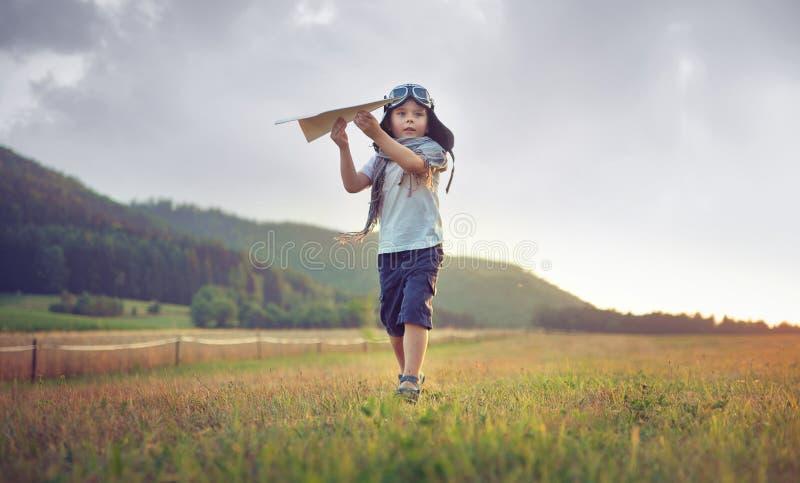 Niño pequeño lindo que juega el avión del juguete imagenes de archivo
