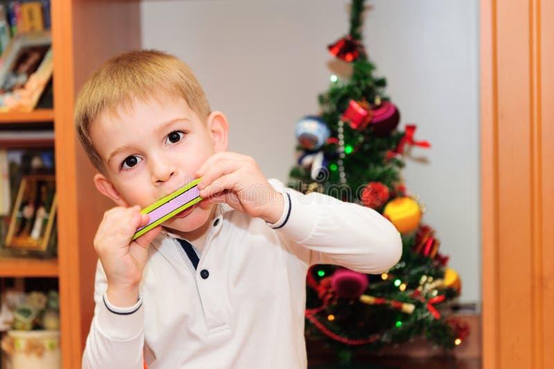 Niño pequeño lindo que juega en la armónica foto de archivo