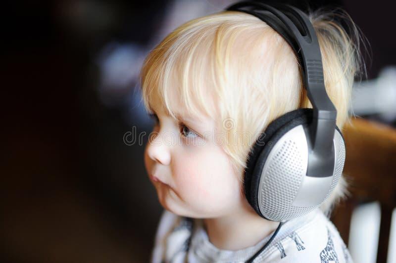 Niño pequeño lindo que lleva los auriculares grandes que escuchan la música imagenes de archivo