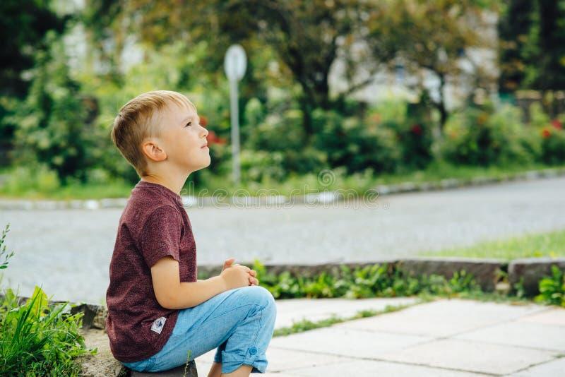 Niño pequeño lindo que mira para arriba el cielo en día soleado Niño que sueña, conceptos de la esperanza fotografía de archivo libre de regalías