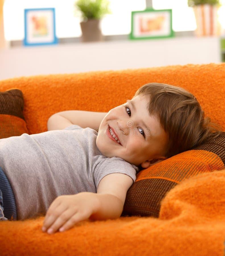 Niño pequeño lindo que ríe en el sofá imagen de archivo libre de regalías