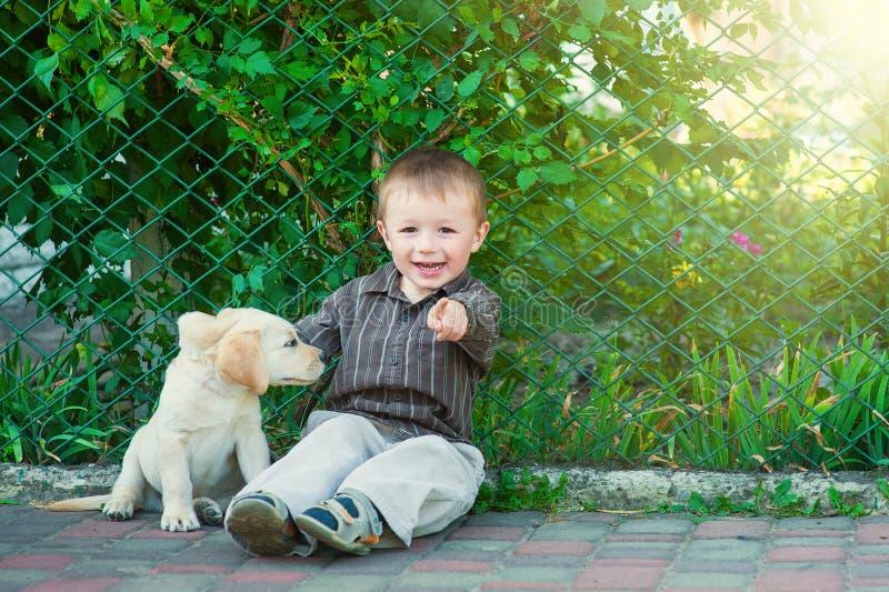 Niño pequeño lindo que se arrodilla con su perrito Labrador que sonríe en la cámara foto de archivo