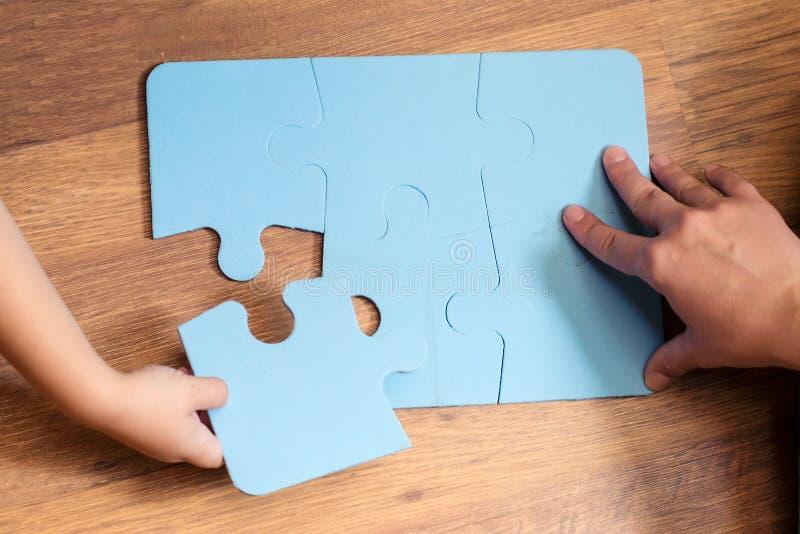 Niño pequeño lindo que soluciona rompecabezas en un piso Educación y desarrollo tempranos imagen de archivo libre de regalías