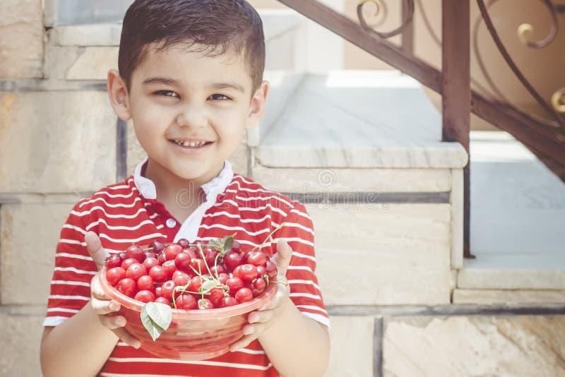 Niño pequeño lindo que sonríe y que sostiene un cuenco de bayas recientemente escogidas de la cereza Copie el espacio Concepto de fotografía de archivo libre de regalías