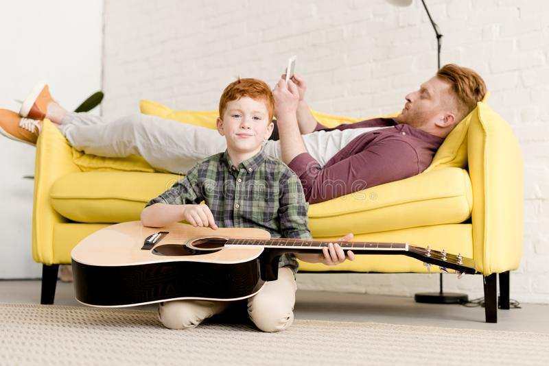 niño pequeño lindo que sostiene el anuncio de la guitarra acústica que sonríe en la cámara mientras que padre usando la tableta d foto de archivo