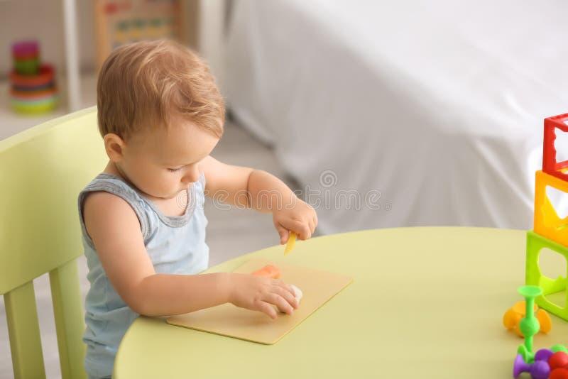 Niño pequeño lindo que usa la pasta del juego en la tabla dentro foto de archivo libre de regalías