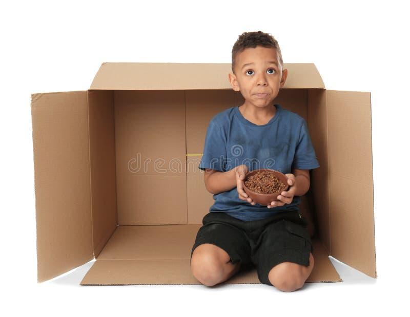 Niño pequeño lindo que vive en caja en el fondo blanco imagen de archivo